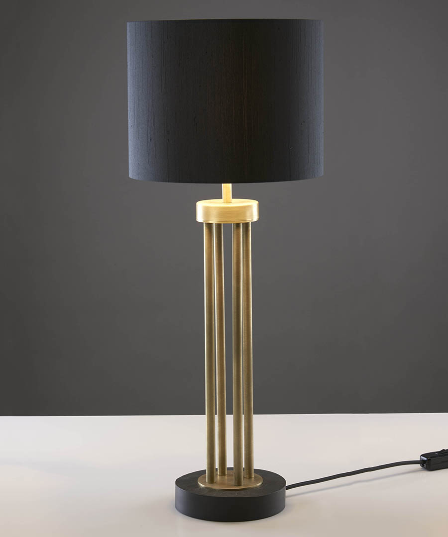 Naxos table light, tall table lamp featuring a stone base and columns in antique brass with a black shade - Chad Lighting